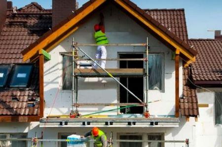 рабочие утепляют пенопластом дом